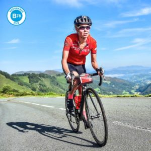 cyclist riding up a hill in the alps with the b78 endurance hub logo on the image
