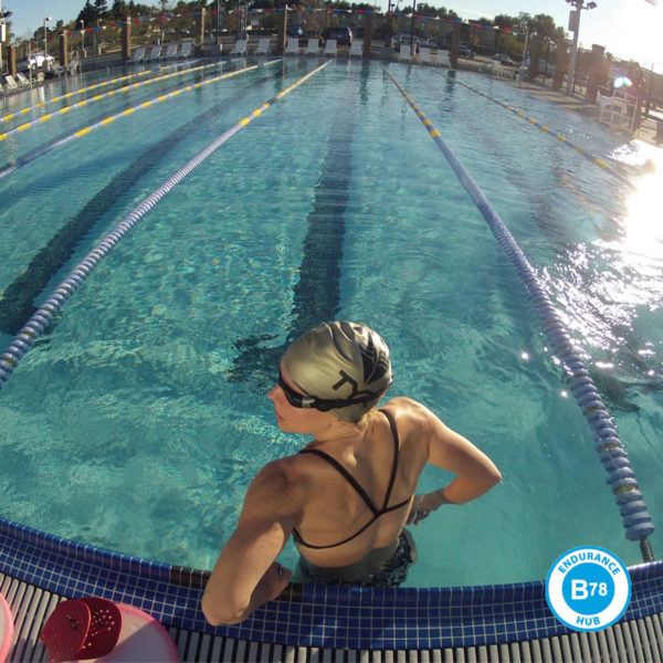 a swimmer stands in a swimming pool getting ready to swim with the b78 endurance hub logo on the image