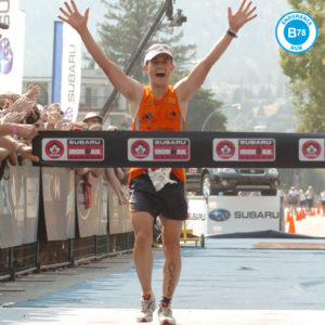 triathlete crossing the finish line at an ironman event with the b78 endurance hub logo on the image