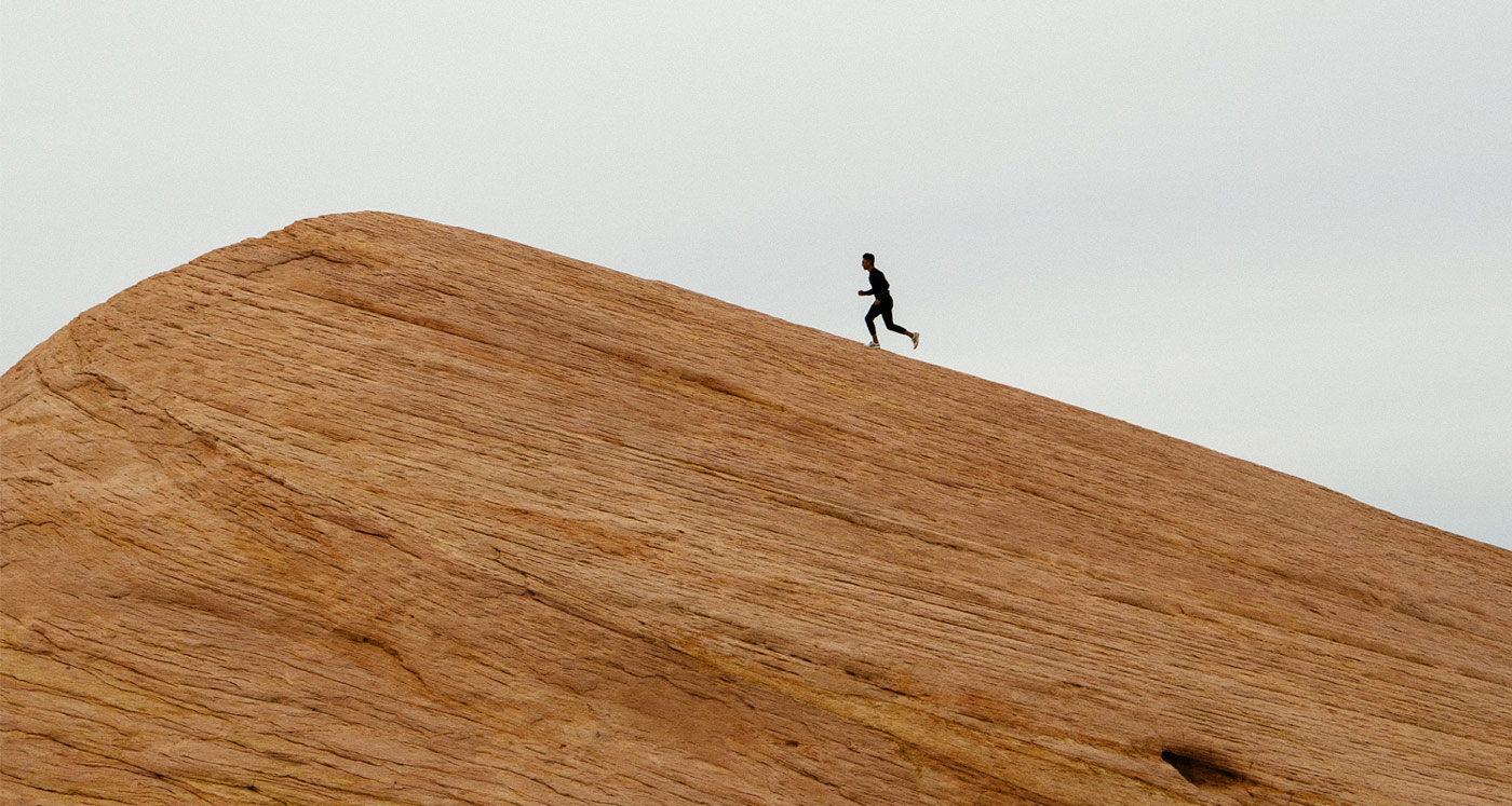 A runner races up a long steep rock slope.