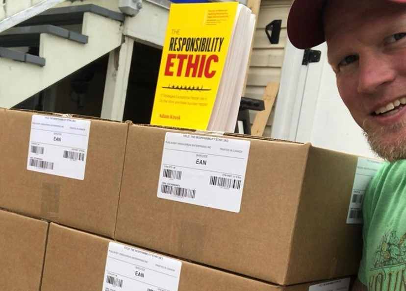 Adam Kreek standing beside a large pallet of boxes that hold his new book The Responsibility Ethic